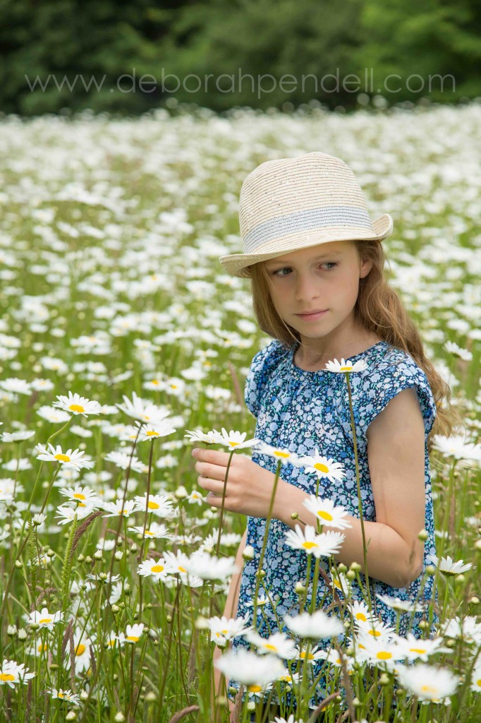 photograph of young girl in daisy field